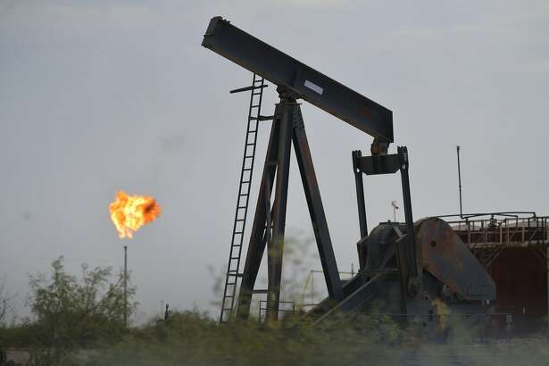 This Sept. 6, 2019 photo shows oil-industry equipment and flares that are common sights in the landscape around Mentone, the sparsely populated town in Loving County in West Texas that is experiencing an oil boom. An estimated 100,000 workers have come to West Texas for the boom, which Ben Shepperd, , president of the Permian Basin Petroleum Association, said is expected to last for decades. (Billy Calzada /The San Antonio Express-News via AP)