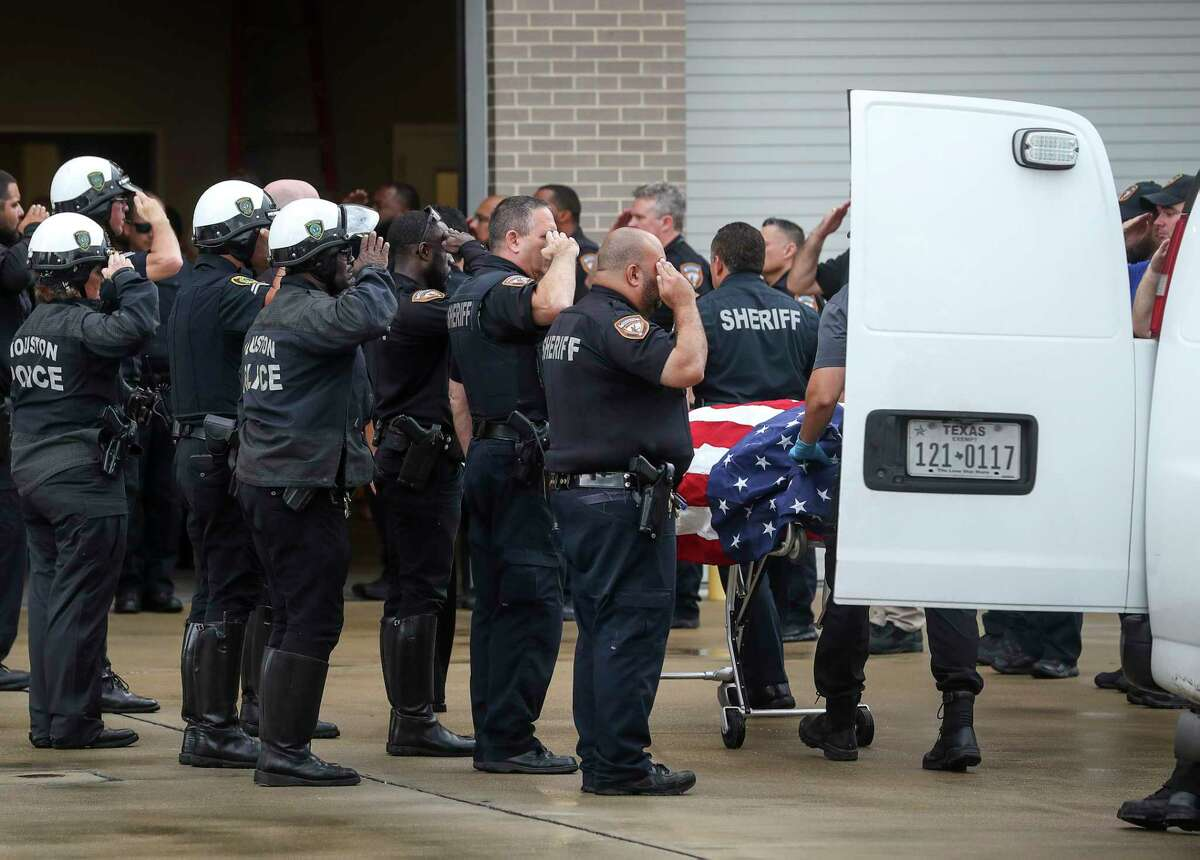 Law enforcement officers escort the body of Deputy Sandeep Dhaliwal, who was shot and killed after a traffic stop in Cypress earlier in the day, to the Harris County Institute of Forensic Sciences on Friday, Sept. 27, 2019, in Houston.