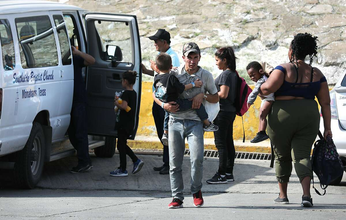 A migrant from Honduras carries his four year-old son in the parking lot of the Mexican Immigration office in Nuevo Laredo. Migrants from Central America and Cuba go to asylum hearings in Laredo, Texas, on Thursday, Sept. 19, 2019.