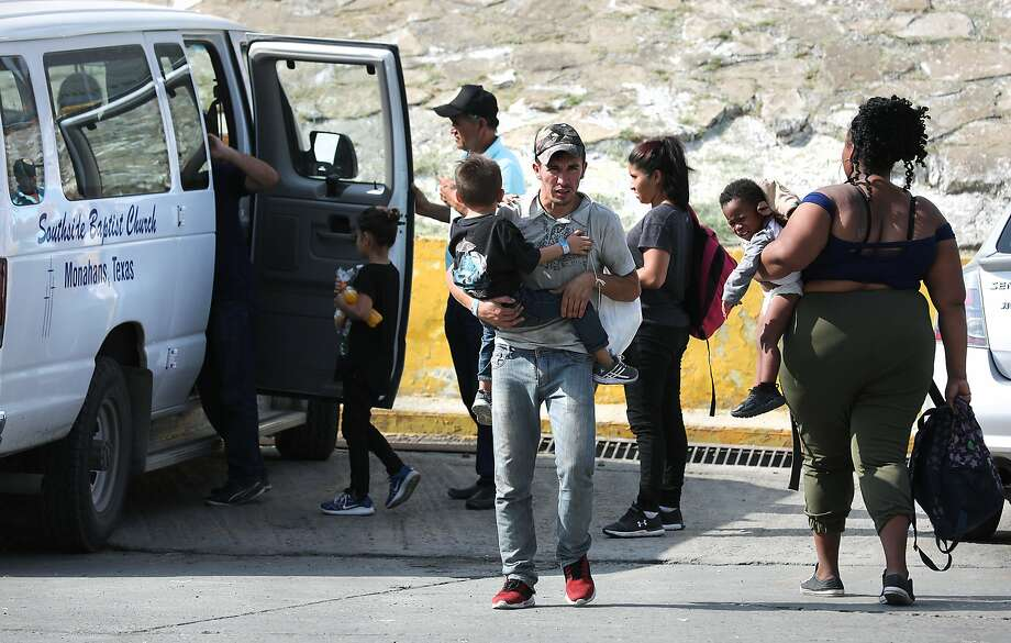 A migrant from Honduras carries his four year-old son in the parking lot of the Mexican Immigration office in Nuevo Laredo. Migrants from Central America and Cuba go to asylum hearings in Laredo, Texas, on Thursday, Sept. 19, 2019. Photo: Bob Owen, Staff Photographer