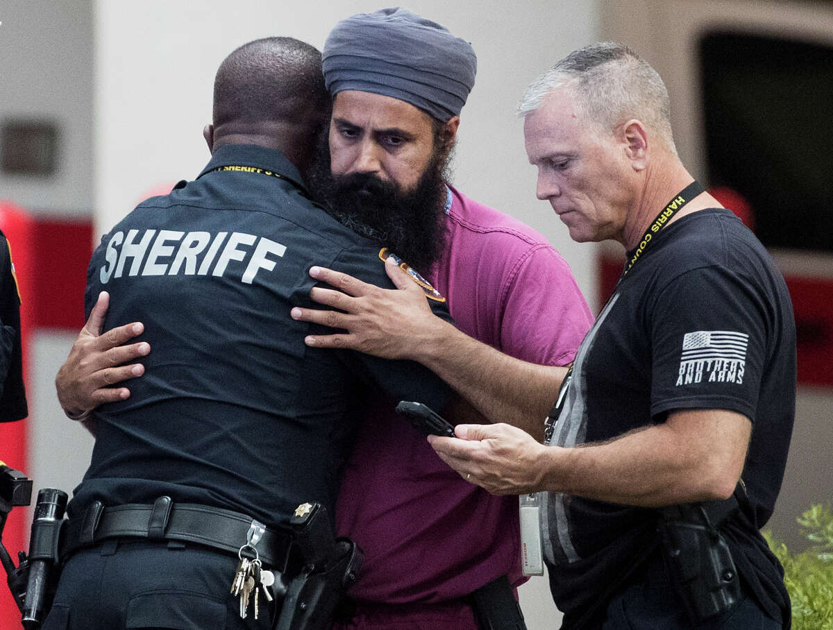 Mourners gather outside Memorial Hermann Hospital after Harris County Sheriff's Deputy Sandeep Dhaliwal was transported to the medical examiners office after was shot and killed in the line of duty on Friday, Sept. 27, 2019, in Houston. Deputy Dhaliwal was shot and killed after a traffic stop in Cypress.