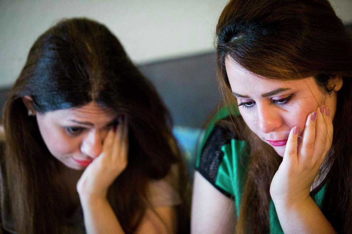 Sarah Ismaeil, left, 31, and her sister Dhuha Ameri, 26, hold back tears back while they speak with their parents in Iraq using a video chat application in August 2018 in Houston. The sisters had been waiting two years for their parents to join them in the United States. The Trump administration's latest 2019 cuts mean many refugees who had been nearing the end of their vetting process likely will not be able to come this year.