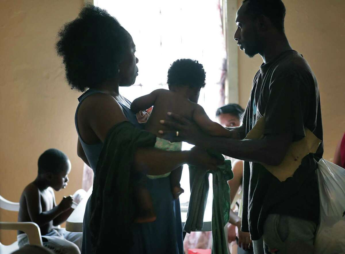 A migrant couple takes care of their children while staying at the Good Samaritan Shelter in Nuevo Laredo. Migrants from Central America and Cuba go to asylum hearings in Laredo, Texas, on Thursday, Sept. 19, 2019.