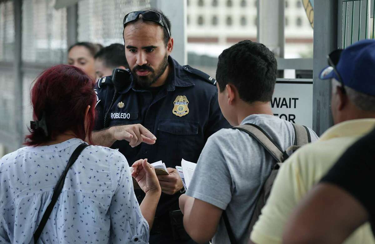 Migrants present their papers to a CBP agent in the middle of Bridge No. 1, on their way for a court hearing in Laredo, Tx on Thursday, Sept. 19, 2019.