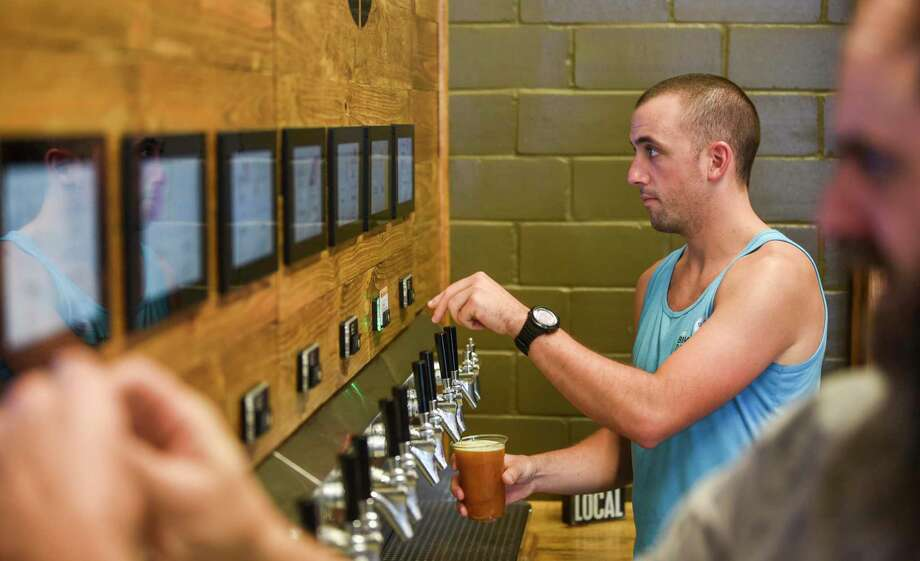 Joe Huyett pours himself a beer from the self-serve tap as he and others enjoy themselves at the grand opening of the Pour Brothers Brewery Friday. Photo taken on Friday, 09/27/19. Ryan Welch/The Enterprise Photo: Ryan Welch, Beaumont Enterprise / The Enterprise / © 2019 Beaumont Enterprise