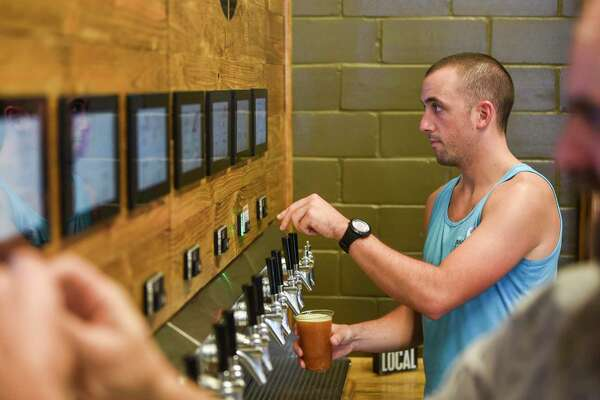 Joe Huyett pours himself a beer from the self-serve tap as he and others enjoy themselves at the grand opening of the Pour Brothers Brewery Friday. Photo taken on Friday, 09/27/19. Ryan Welch/The Enterprise