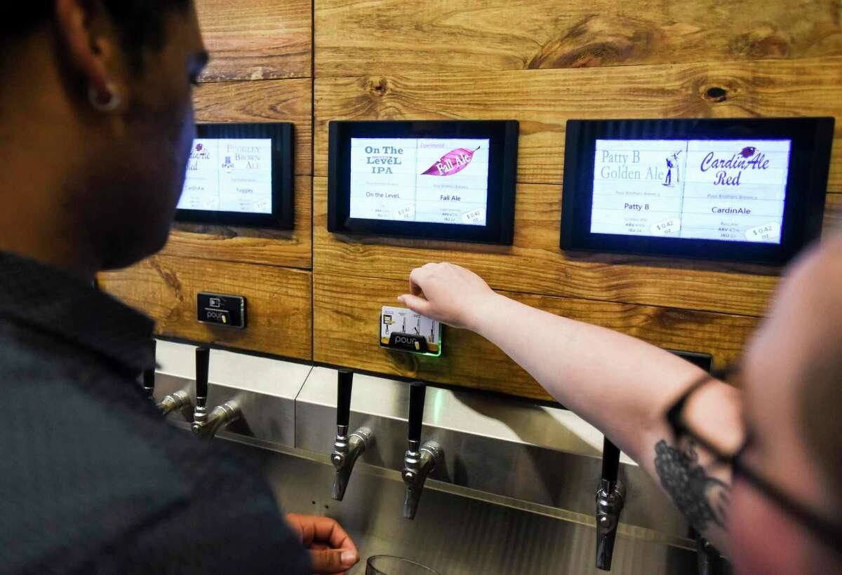 Mitchell Junious gets assistance from Kayleigh Thompson as she shows Junious how to operate the self-serve tap at the grand opening of the Pour Brothers Brewery Friday. Photo taken on Friday, 09/27/19. Ryan Welch/The Enterprise