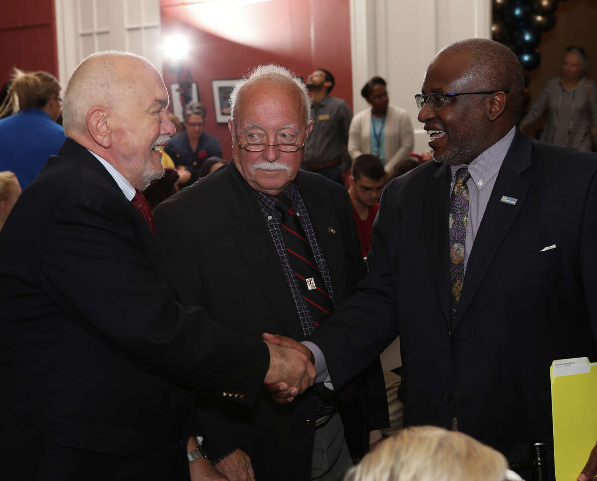 Dr. Steady Moono, President of SUNY Schenectady, greets Thomas Baker (shaking hands) and Alan Carter, two of the College's Founding Faculty Members, who joined in the festivities during the Collegea€™s 50th Anniversary Celebration, held Sept. 17 on campus. (Photo by Denis J. Nally)