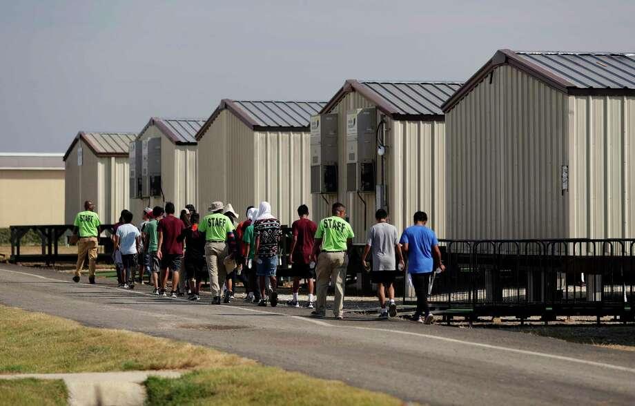 Fotografía de archivo del 9 de julio de 2019 de empleados escoltando a jóvenes a clases en el centro de detención más nuevo del gobierno de Estados Unidos para menores migrantes en Carrizo Springs, Texas. Photo: Eric Gay /Associated Press / Copyright 2019 The Associated Press. All rights reserved.