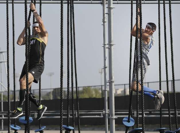 "Air Force Capt. Noah Palicia (right) and his brother, U.S. Army Lt. Col. Eric Palicia both compete on the ""Sea of Ropes"" as members of the Armed Forces compete in the 2nd annual Alpha Warrior Inter-Service Battle at Retama Park on Saturday, Sept. 14, 2019. 26 competitors were dwindled down to 16 finalists as men and women from the Army, Navy and Air Force ran, pushed, crawled, jumped and lifted themselves through 36 obstacles on the course that tested their strength, endurance and agility. Some zipped through the course while others fought fatigue and exhaustion to get to the finish line as fellow service members cheered and rooted them on during every challenge. In the end, the team from the Air Force finished with the best combined time to take the overall win. Noah finished with a quicker time of 21:05.1 over his brother, Eric, who finished 22:29.1.(Kin Man Hui/San Antonio Express-News) Photo: Kin Man Hui/Staff Photographer"