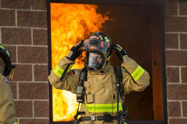 A cadet adjusts their helmet in a demonstration during the San Antonio Fire Department Cadet Class 19A family day at the San Antonio Fire Department Training Academy in San Antonio on Monday, Sept. 18, 2019. After completing 26 weeks of training, the academy will graduate 24 cadets Sept. 20, to become the newest probationary firefighters. Photo: Daniel Carde/Special Contributor