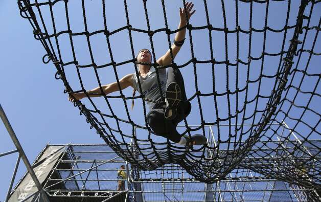 "Air Force 2nd Lt. Arielle Miller completes the ""Alcatraz"" obstacle as members of the Armed Forces compete in the 2nd annual Alpha Warrior Inter-Service Battle at Retama Park on Saturday, Sept. 14, 2019. 26 competitors were dwindled down to 16 finalists as men and women from the Army, Navy and Air Force ran, pushed, crawled, jumped and lifted themselves through 36 obstacles on the course that tested their strength, endurance and agility. Some zipped through the course while others fought fatigue and exhaustion to get to the finish line as fellow service members cheered and rooted them on during every challenge. In the end, the team from the Air Force finished with the best combined time to take the overall win. (Kin Man Hui/San Antonio Express-News) Photo: Kin Man Hui/Staff Photographer"