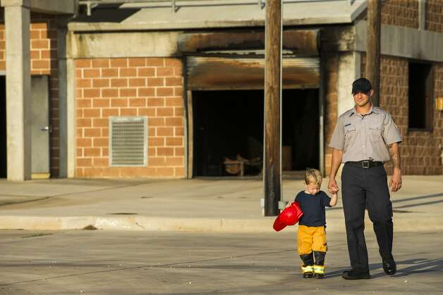 Abel Brooks, 2, walks with his father, Caleb Scott, 28, during the San Antonio Fire Department Cadet Class 19A family day at the San Antonio Fire Department Training Academy in San Antonio on Monday, Sept. 18, 2019. After completing 26 weeks of training, the academy will graduate 24 cadets Sept. 20, to become the newest probationary firefighters. Photo: Daniel Carde/Special Contributor