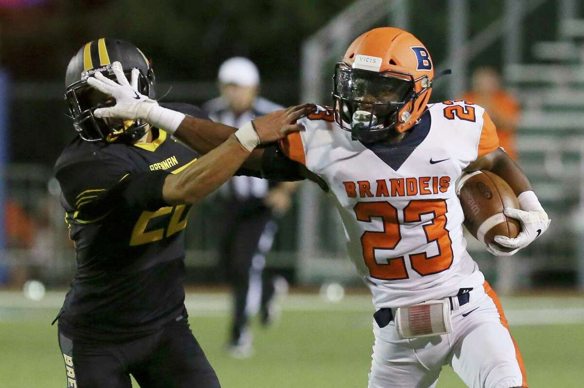 Brandeis' Frank Wilson IV, right, stiff-arms Brennan's Jonathan Swisher during a kick return of the Broncos' rout of the Bears in 28-6A action Friday at Farris Stadium.