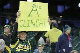 "A fan holds a sign that reads ""A's Clinch!"" before a baseball game between the Seattle Mariners and the Oakland Athletics, Friday, Sept. 27, 2019, in Seattle. The Athletics clinched a wild-card berth in the American League before the first pitch of their game when the Cleveland Indians lost to the Washington Nationals. (AP Photo/Ted S. Warren)"