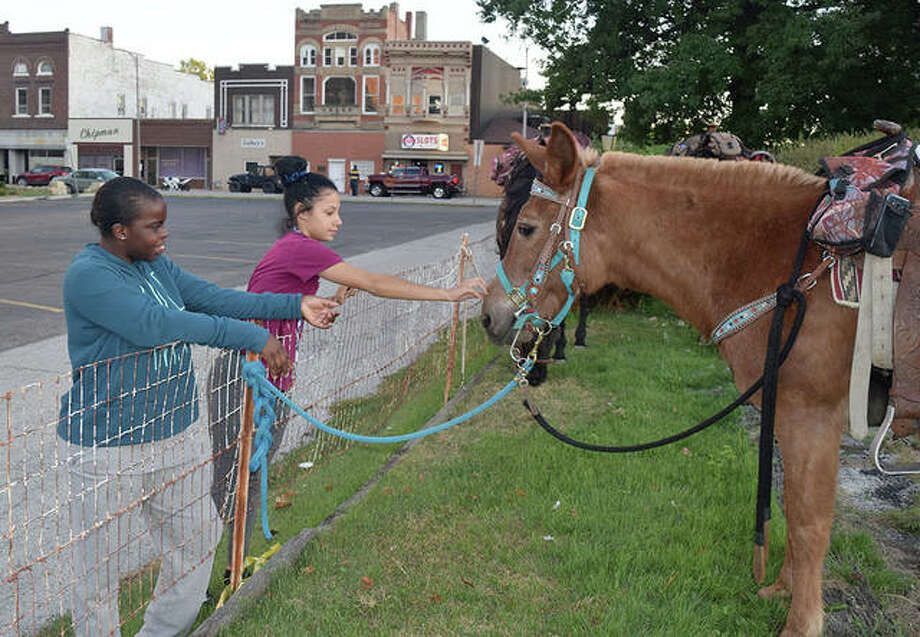 Desmoria Walton, 15, of Jacksonville (left) and Justiss Banks, 16, of Jacksonville pet horses that were hitched Thursday near West State Street. Photo: Marco Cartolano | Journal-Courier