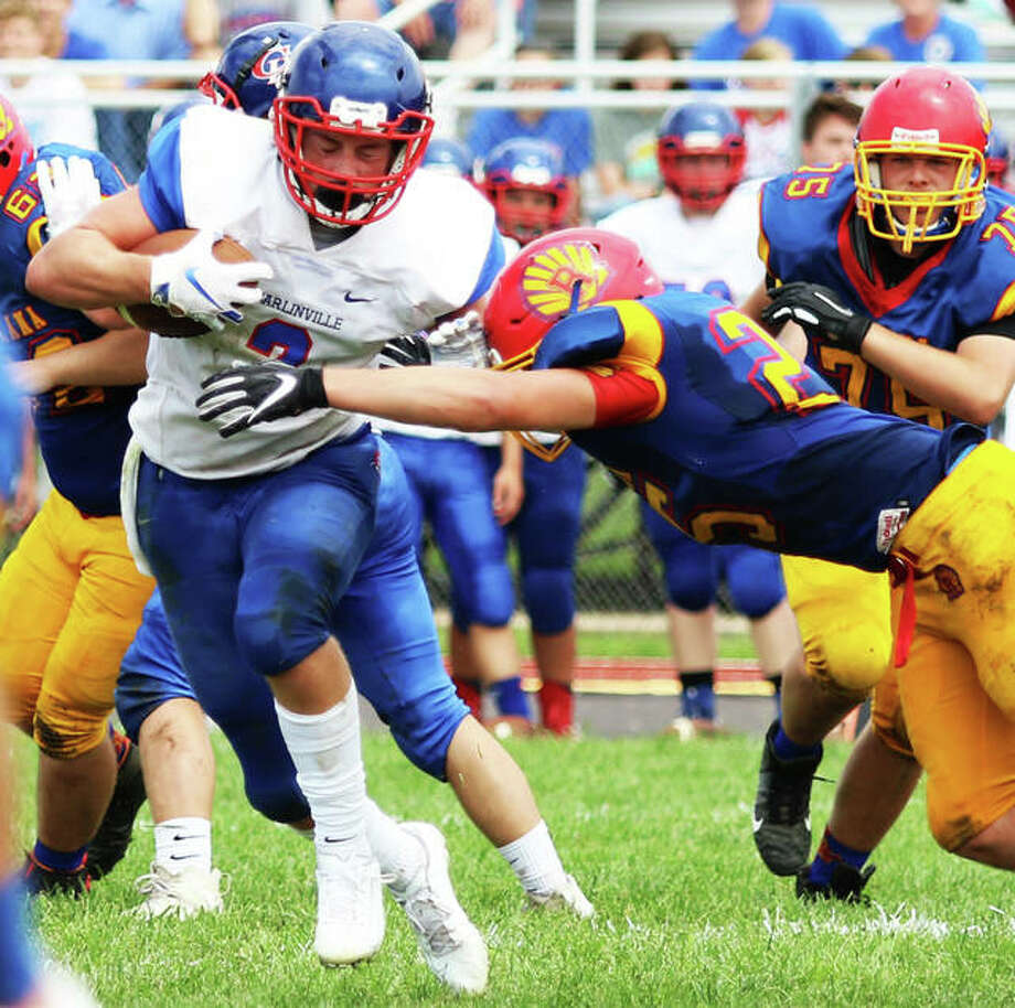 Carlinville's Colton DeLong (left), shown trying to elude Roxana's David Pluester in a SCC game in Week 1 at Roxana, rushed for 232 yards and four touchdowns Friday night in the Cavaliers' SCC victory over Staunton in Carlinville. Photo: Greg Shashack / The Telegraph