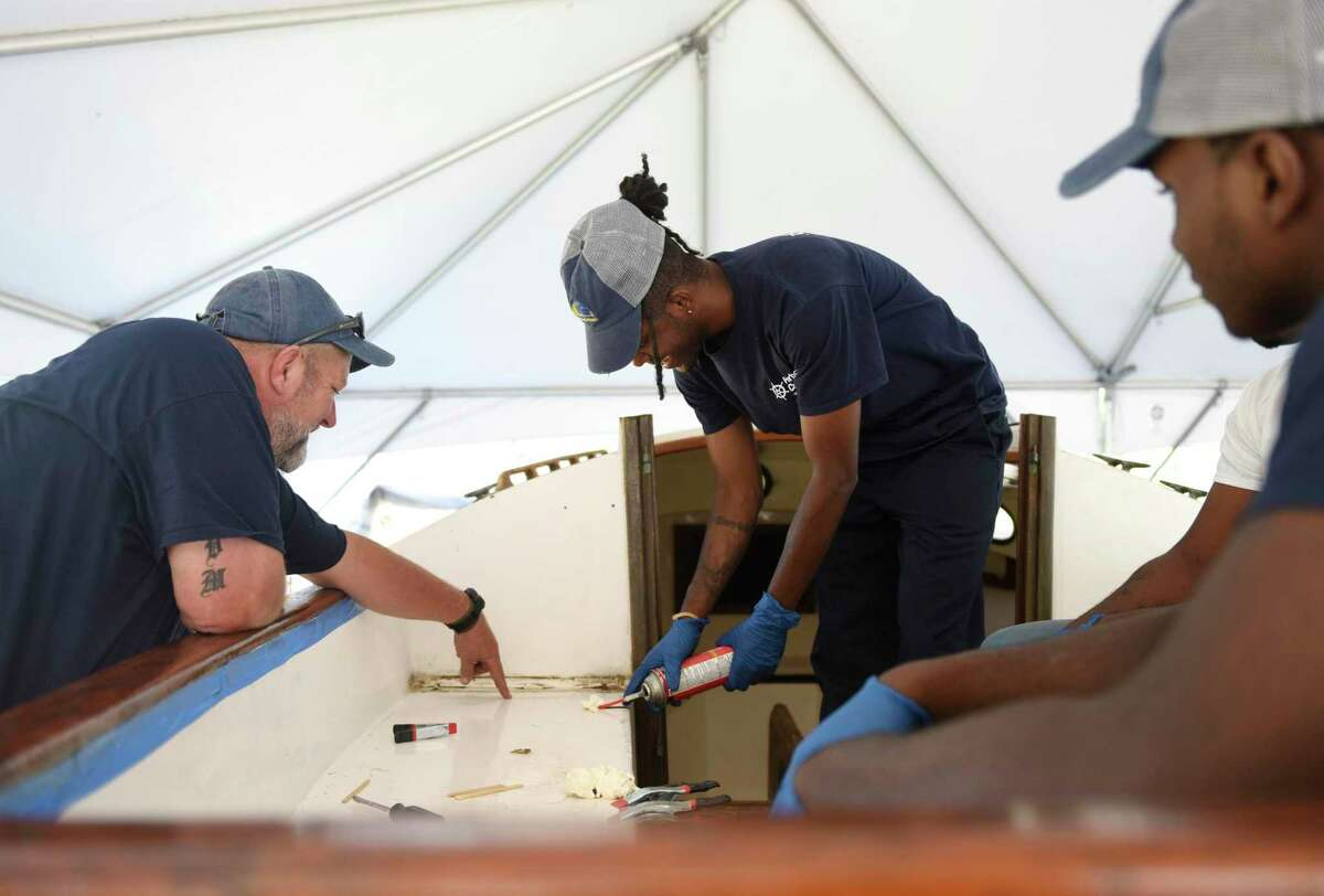 Program instructor Josh Mayo, left, works with recent high school graduates Donovan Carter, center, and Jeremiah Davis to restore a boat at the SoundWaters Harbor Corps marine job training program at John J. Boccuzzi Park in Stamford, Conn. Thursday, Sept. 26, 2019. In partnership with DOMUS, recent Stamford Public Schools graduates learn valuable technical skills and connect with marine industry leaders to learn of career opportunities on the Stamford waterfront. This fall, members are restoring a catboat, and in the process learning fiberglass repair, carpentry, painting, varnishing, rigging, engine maintenance and more.