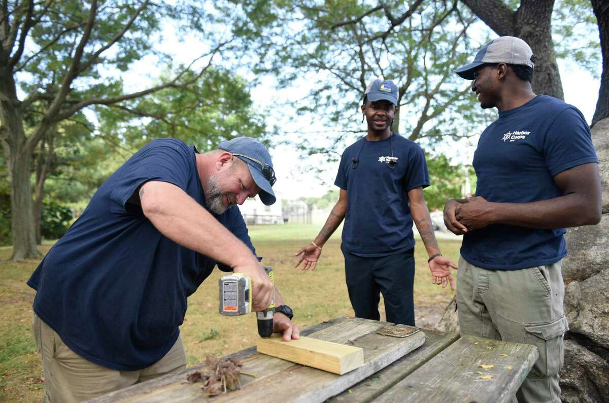 Program instructor Josh Mayo, left, works with recent high school graduates Donovan Carter, center, and Jeremiah Davis at the SoundWaters Harbor Corps marine job training program at John J. Boccuzzi Park in Stamford, Conn. Thursday, Sept. 26, 2019. In partnership with DOMUS, recent Stamford Public Schools graduates learn valuable technical skills and connect with marine industry leaders to learn of career opportunities on the Stamford waterfront. This fall, members are restoring a catboat, and in the process learning fiberglass repair, carpentry, painting, varnishing, rigging, engine maintenance and more.