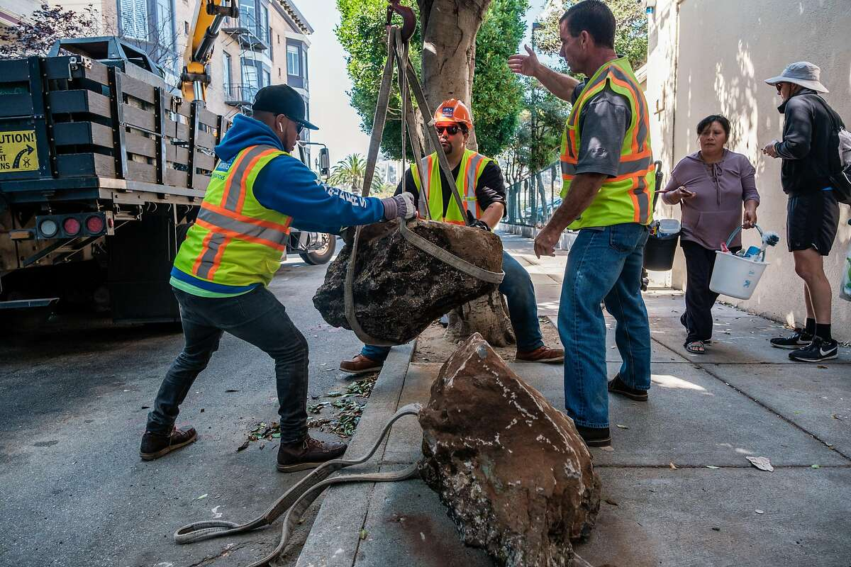 City workers lift boulders back onto to the sidewalk after they were moved from the sidewalk to the street in San Francisco, Calif. on Saturday, September 28, 2019. The boulders are meant to deter homeless encampments on the sidewalk.