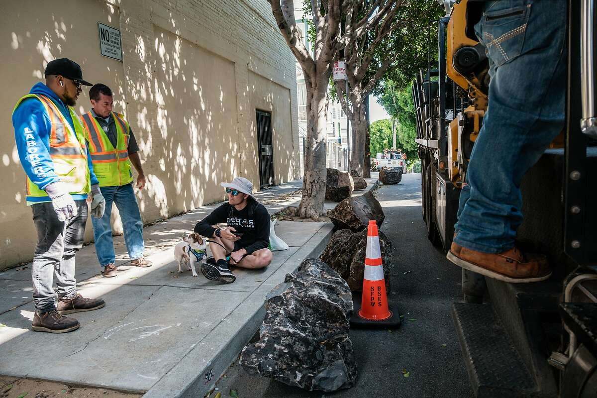 City workers speak to a man unidentified man who refused to move so they could lift boulders back onto to the sidewalk after they were moved from the sidewalk to the street in San Francisco, Calif. on Saturday, September 28, 2019. The boulders are meant to deter homeless encampments on the sidewalk.