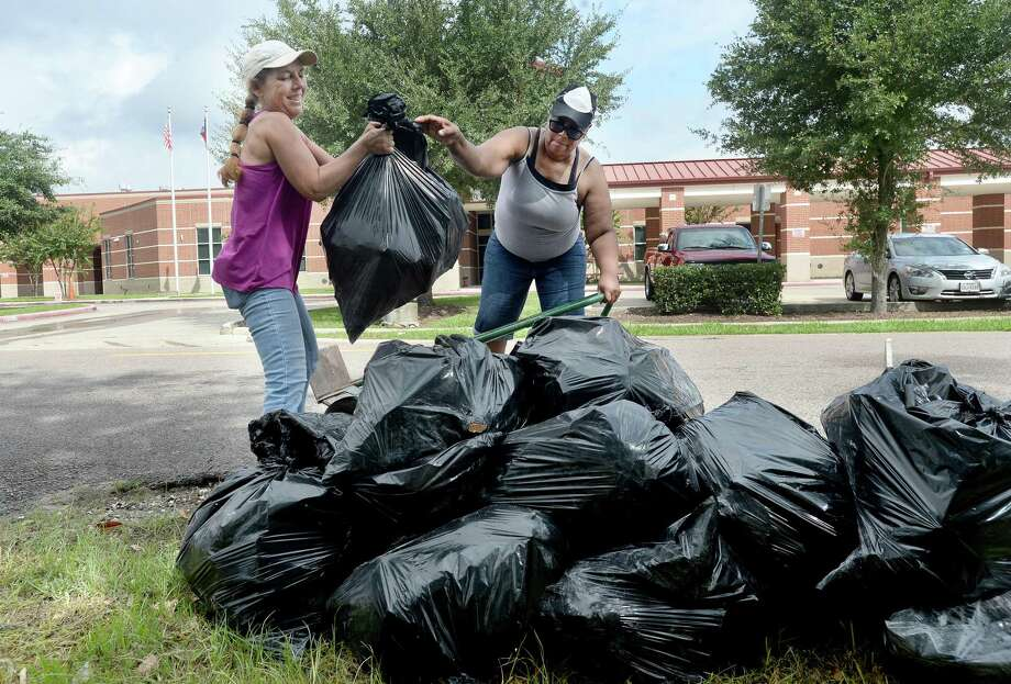 Stacey Fleming (left) helps Felecia Romar unload bags filled with debris as she helps gut Romar's parents' home on Blanchette Street Saturday. Fleming is a contractor who has helped gut and rebuild homes since Harvey, and came to Beaumont to help those in need, including Preella and Ernest Romar, after getting a facebook message from Felecia.City trucks were also spread throughout the neighborhood surrounding Fehl - Price Elementary to continue large debris pick-up from homes and businesses gutted after flooding during Imelda last week. Photo taken Saturday, September 28, 2019 Kim Brent/The Enterprise Photo: Kim Brent / The Enterprise / BEN