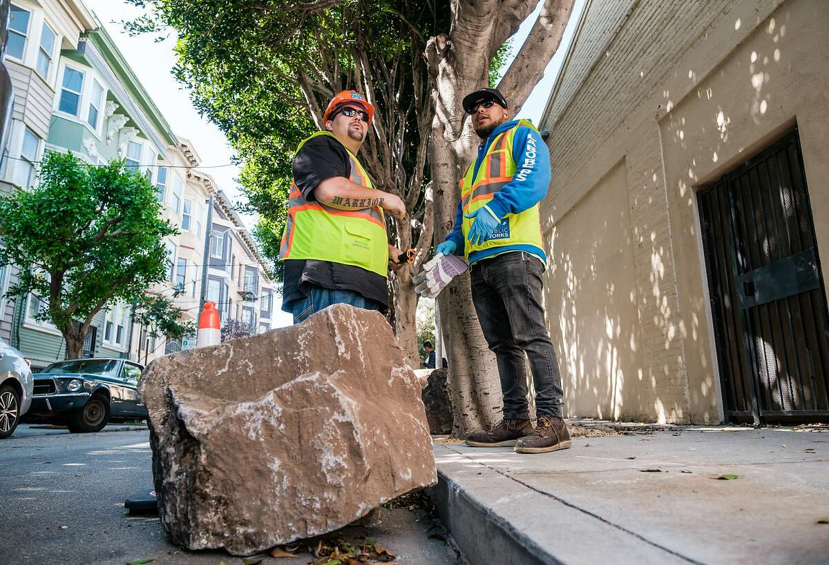 City workers prepare to lift boulders back onto to the sidewalk after they were moved to the street, in San Francisco on September 28, 2019. The boulders are meant to deter homeless encampments on the sidewalk.