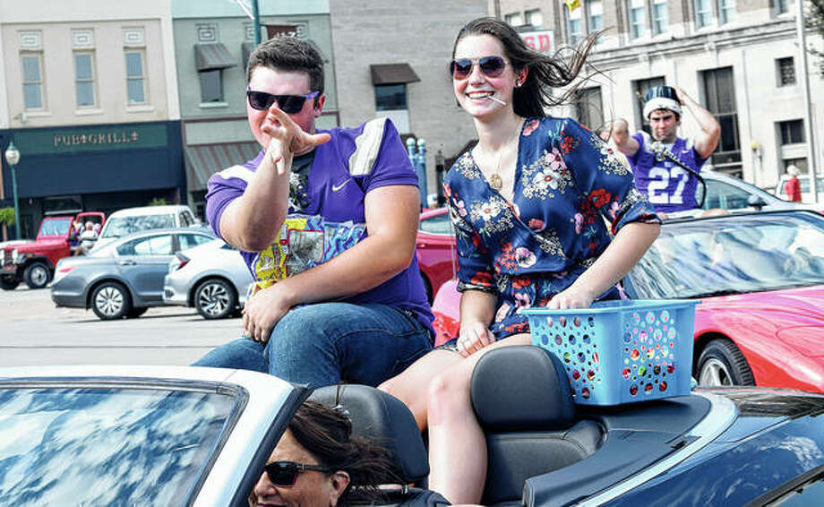 Routt Catholic High School students and homecoming court members Clayton Costello (left) and Sydney Walker (right) throw candy to onlookers Friday during the school's homecoming parade. Photo: Marco Cartolano | Journal-Courier