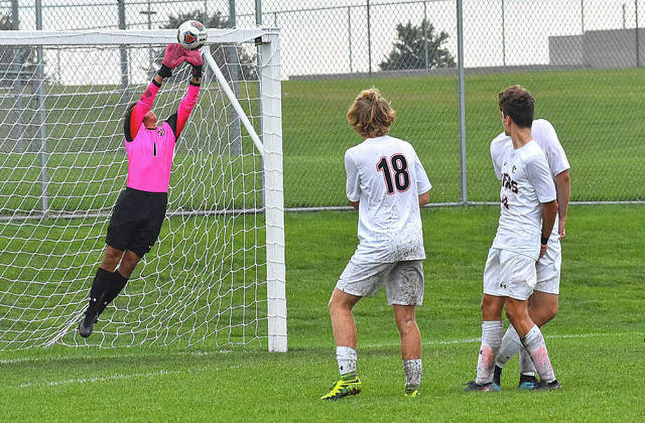 Edwardsville keeper Tyler Frolik makes a save off a free kick with a wall of Tigers watching the play develop in the second half on Saturday in Normal. Photo: Matt Kamp|The Intelligencer