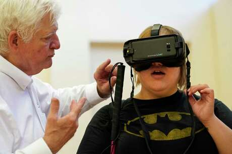 "Mark Mathew, left, with Christal Vision helps Mandy Ordonez tries on IrisVision, a wearable enhancement device for people with low vision, during the Annual Disability Unity and Pride Celebration held at West Gray Multiservice Center: 1475 W Gray St., Saturday, Sept. 28, 2019, in Houston. After trying out the adaptive technology, Ordonez said, ""It is awesome. I could see things far away."" The event hosted by the Mayor's Office for People with Disabilities featured performances, awards, and community resources."