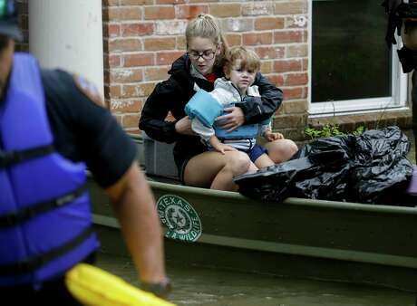 A woman and small child sit on a Texas Game Warden boat after evacuating a flooded home in the Lochshire neighborhood Friday, Sept. 20, 2019, in Huffman, Texas. The Luce Bayou overflowed due to the heavy rain during Tropical Storm Imelda.