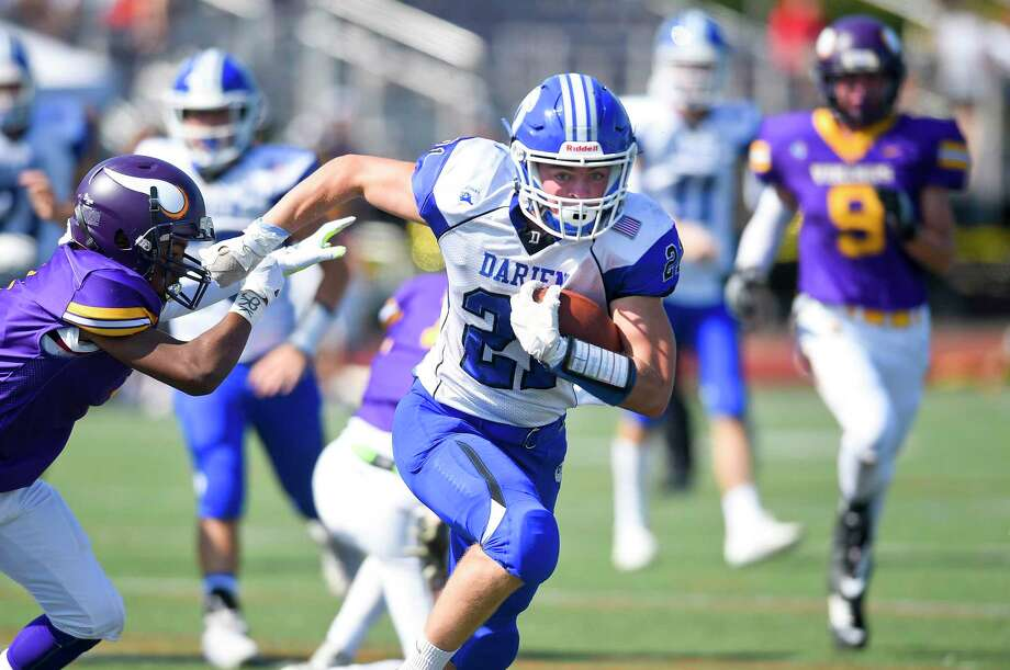 Darien's Will Kirby (21) breaks upfield in an FCIAC football game against Westhill at Westhill High School's J. Walter Kennedy Stadium on Sept. 28, 2019 in Stamford, Connecticut. Photo: Matthew Brown / Hearst Connecticut Media / Stamford Advocate