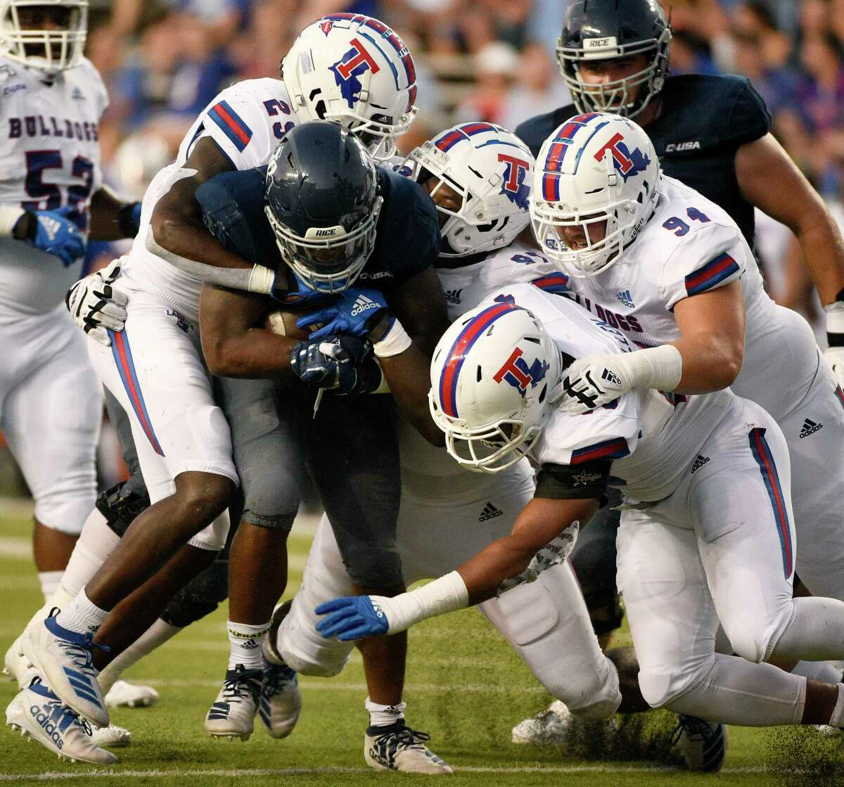 Rice running back Aston Walter, bottom left, is tackled by Louisiana Tech safety Bee Jay Williamson, left, and teammates during the first half of an NCAA college football game, Saturday, Sept. 28, 2019, in Houston.