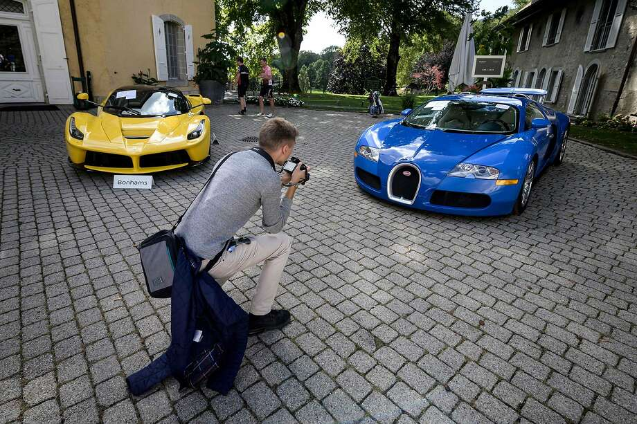 A 2015 Ferrari LaFerrari (left) and a 2010 Bugatti Veyron EB 16.4 Coupe are displayed before the auction near Geneva of sport cars belonging to the son of Equatorial Guinea's president. Photo: Fabrice Coffrini / AFP / Getty Images