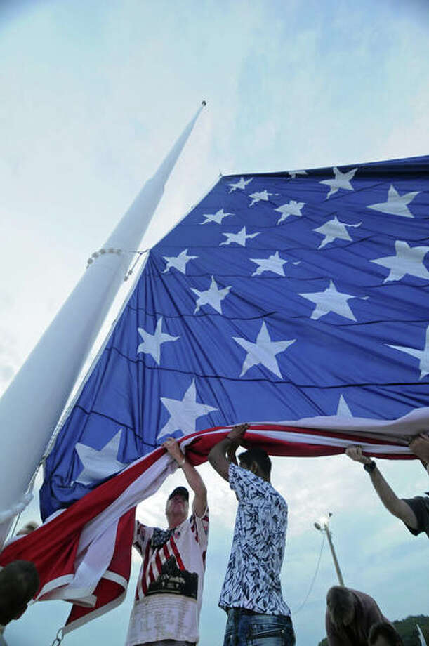 A team of veterans and first responders begin to hoist a giant flag in Grafton for the first time on Saturday. An estimated 1,000 people attended the ceremony for the 40-by-80-foot American flag that will fly from a 130-foot flag pole in Grafton Lighthouse Park at the confluence of the Mississippi and Illinois Rivers.
