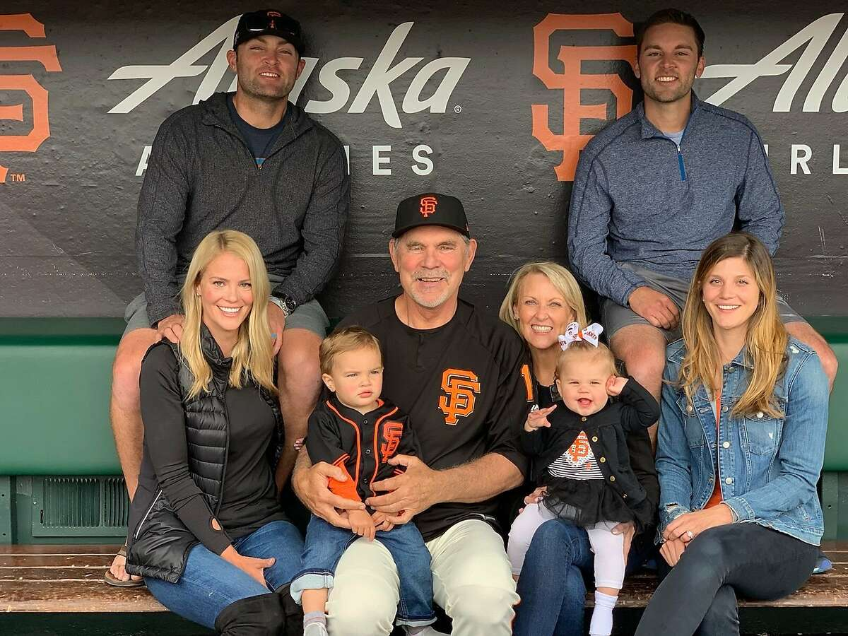 The Bochy family poses for a picture in the dugout at Oracle Park in San Francisco on August 29, 2019: San Francisco Giants manager Bruce Bochy with his wife, Kim (center left / center right), their son, Greg (upper left) with his wife McKenna (bottom left) and their son Braxton (on Bruce Bochy's lap). The Bochys' other son, former Giants pitcher Brett (upper right) with his wife, Kelsey (bottom right), and their daughter, Blakely (on Kim Bochy's lap).
