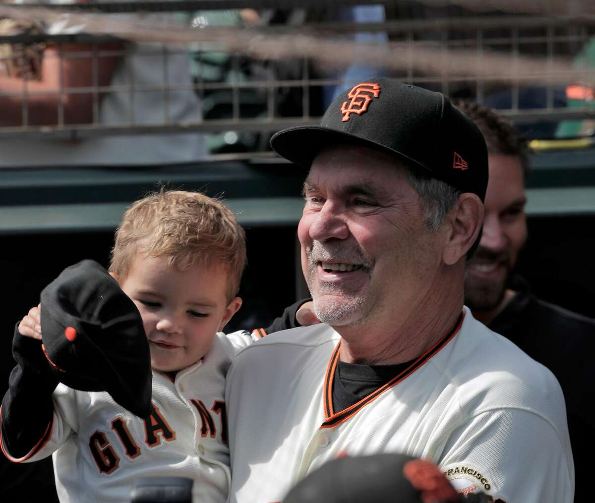 Bruce Bochy holds his grandson in the dugout before he managed his final game with the San Francisco Giants at Oracle Park in San Francisco, Calif., on Sunday, September 29, 2019.
