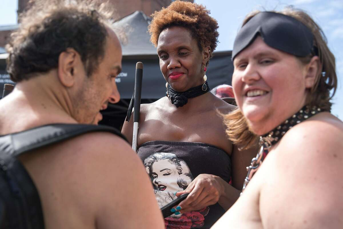 Amy Mason, right, Jim Barbour and Bobbi Pompey, center, partake in the 35th annual Folsom Street Fair, a celebration of alternative sexuality and fetish culture. On Sunday, September 29, 2019. San Francisco, Calif.