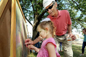 Charlotte McIntosh, 2, of Edwardsville gets a little creative help from her grandfather John Nitchman of Glen Carbon, as they use colored chalk on a chalkboard Saturday during the 2019 Edwardsville Art Fair at City Park.