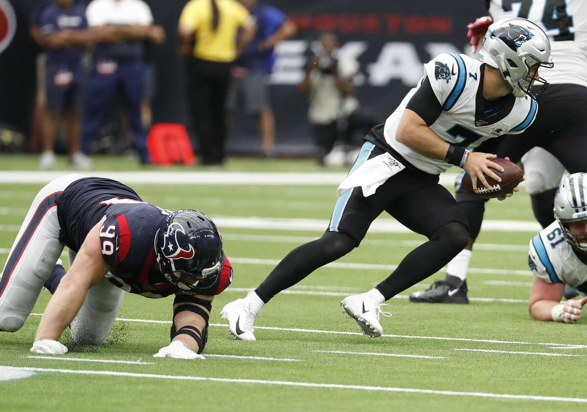 Carolina Panthers quarterback Kyle Allen (7) escapes the grasp of Houston Texans defensive end J.J. Watt (99) behind the line of scrimmage during an NFL football game at NRG Stadium on Sunday, Sept. 29, 2019, in Houston. After escaping the potential sack, Allen completed a pass for a first down.