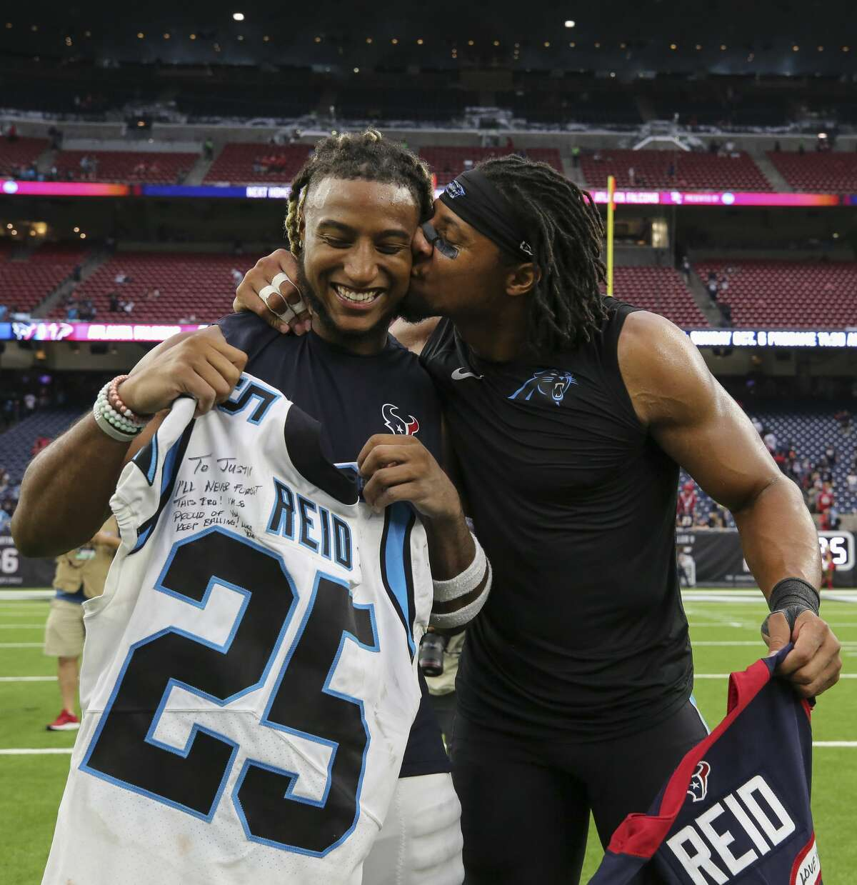 Carolina Panthers strong safety Eric Reid (25), right, gives a kiss to his brother Houston Texans strong safety Justin Reid (20) after exchanging jerseys after an NFL game at NRG Stadium Sunday, Sept. 29, 2019, in Houston. The Panthers won 16-10.