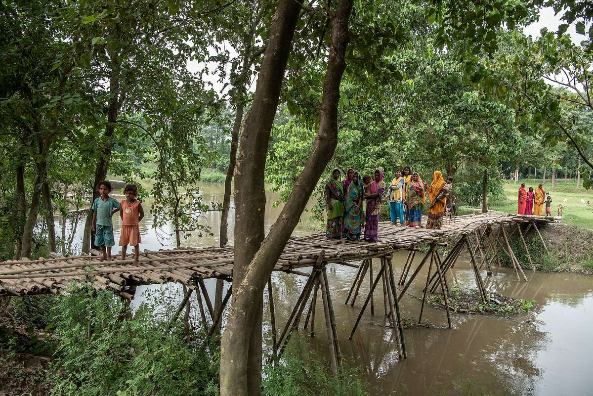 Residents of a village near the Bagmati River stand over a handmade bridge which survived the floods, Sept. 19, 2019. This summer's flash floods played out differently Nepal's border with India as embankments blocked swollen upstream rivers from emptying south, leaving Nepal to deal with two or three times more flooding than India in some areas, according to local officials. (Saumya Khandelwal/The New York Times)