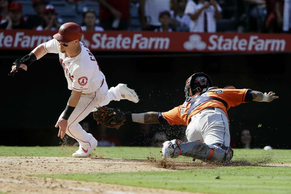 Los Angeles Angels' Kole Calhoun eludes the tag by Houston Astros catcher Martin Maldonado to score on a double by Andrelton Simmons during the eighth inning of a baseball game in Anaheim, Calif., Sunday, Sept. 29, 2019. (AP Photo/Alex Gallardo)