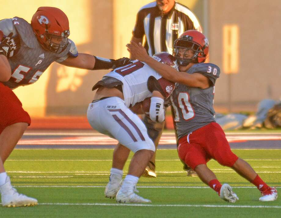 Plainview players Ben Hernandez and Charles Gipson attempt to bring down Hereford ball carrier Xavier Gonzalez during their non-district football game on Friday at Greg Sherwood Memorial Bulldog Stadium. Photo: Nathan Giese/Planview Herald