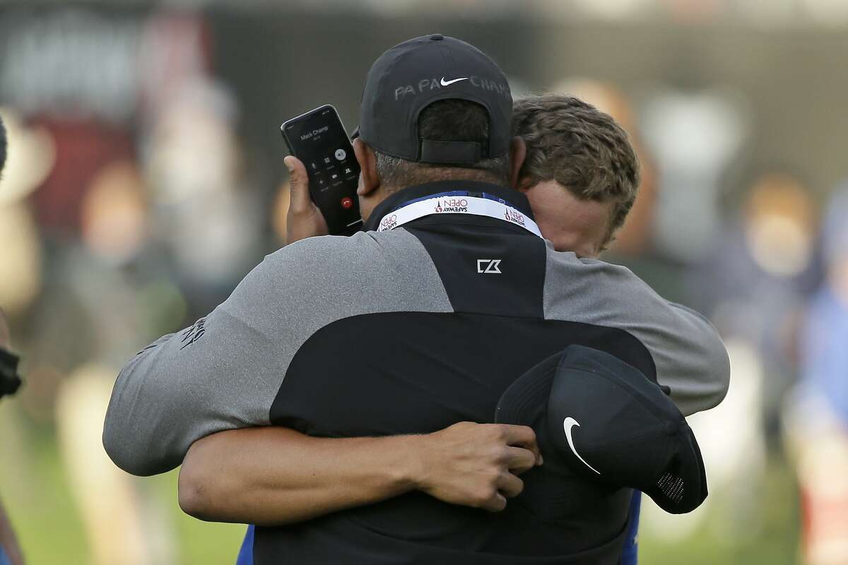 Cameron Champ, right, talks with his grandfather while being embraced by his father, Jeff Champ, on the 18th green of the Silverado Resort North Course after winning the Safeway Open PGA golf tournament Sunday, Sept. 29, 2019, in Napa, Calif. Champ's grandfather is in hospice battling cancer. (AP Photo/Eric Risberg)