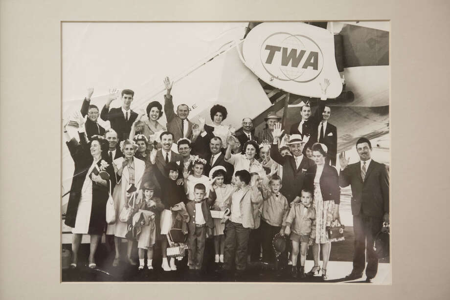 An older image with several families posing together, dressed up, to take a Fugazi-booked charter plane to Italy. Photo: Blair Heagerty / SFGate