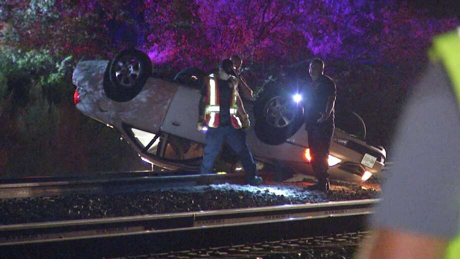 One woman was hospitalized after rolling her vehicle onto a set of train tracks. Photo: Ken Branca