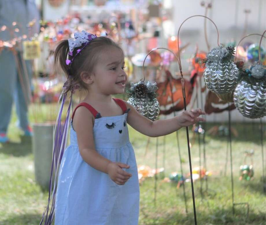 Willow Losey was one of several attendees of the annual Labor Day Arts and Crafts festival to take a liking to lawn ornaments in a variety of shapes, designs and colors. (Pioneer photos/Taylor Fussman)