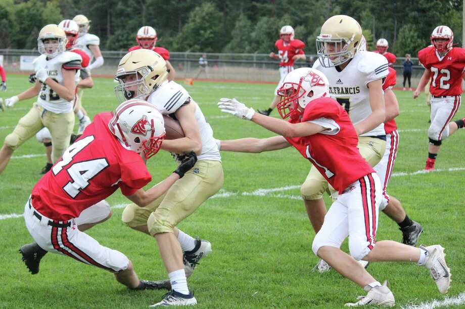 Benzie Central's Dylan Chrzanowski (44) and Cael Katt (1) team up to bring down the St. Francis ball carrier on the play. (Photo/Robert Myers)