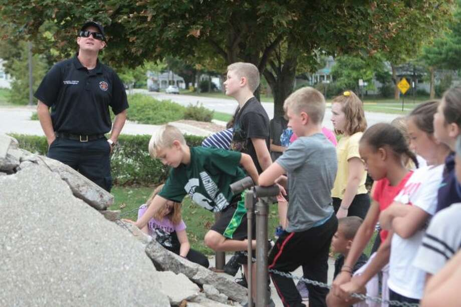 Members of Tonya Morgan's Big Rapids Middle School fifth-grade class visited the Big Rapids Department of Public Safety on Wednesday to commemorate the 18th anniversary of the events of Sept. 11, 2001. Firefighter Sean Wethington explained the 9/11 memorial in front of the department is made of a steel beam that once was a part of the World Trade Center. (Pioneer photo/Taylor Fussman)